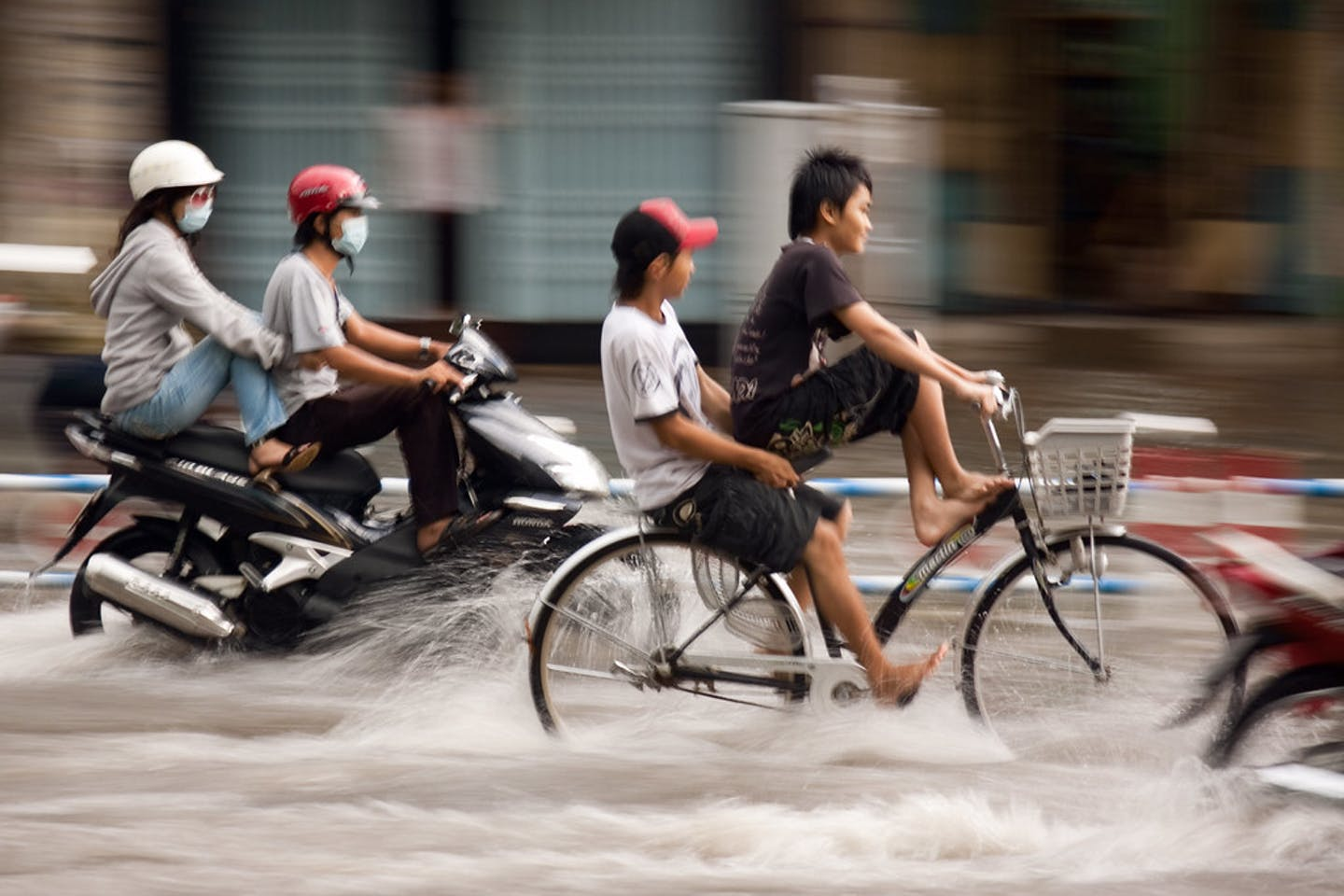 Bikers ride through flood in Vietnam.