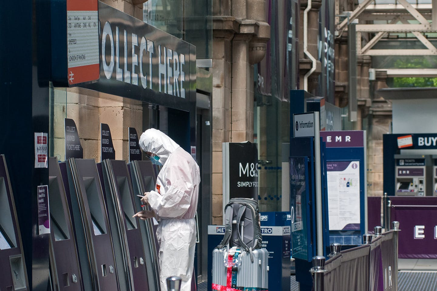 traveller in a protective suit  withdraws cash coronavirus