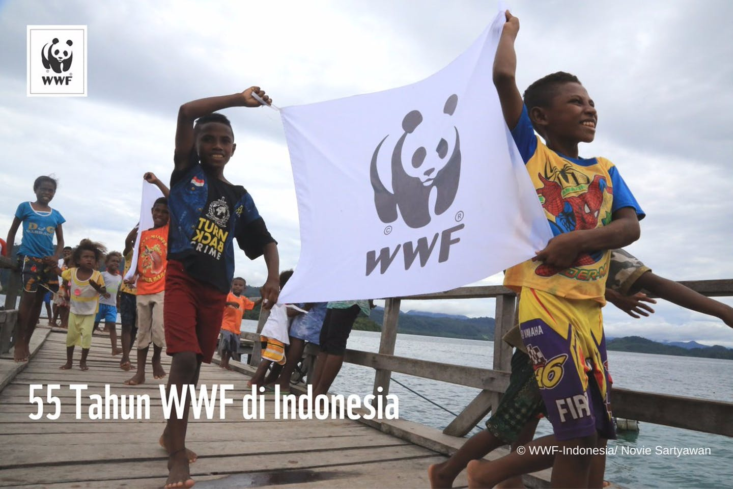 Children hold a WWF banner to celebrate 55 years of operations for the NGO in Indonesia. Image: WWF-Indonesia/Novie Sartyawan