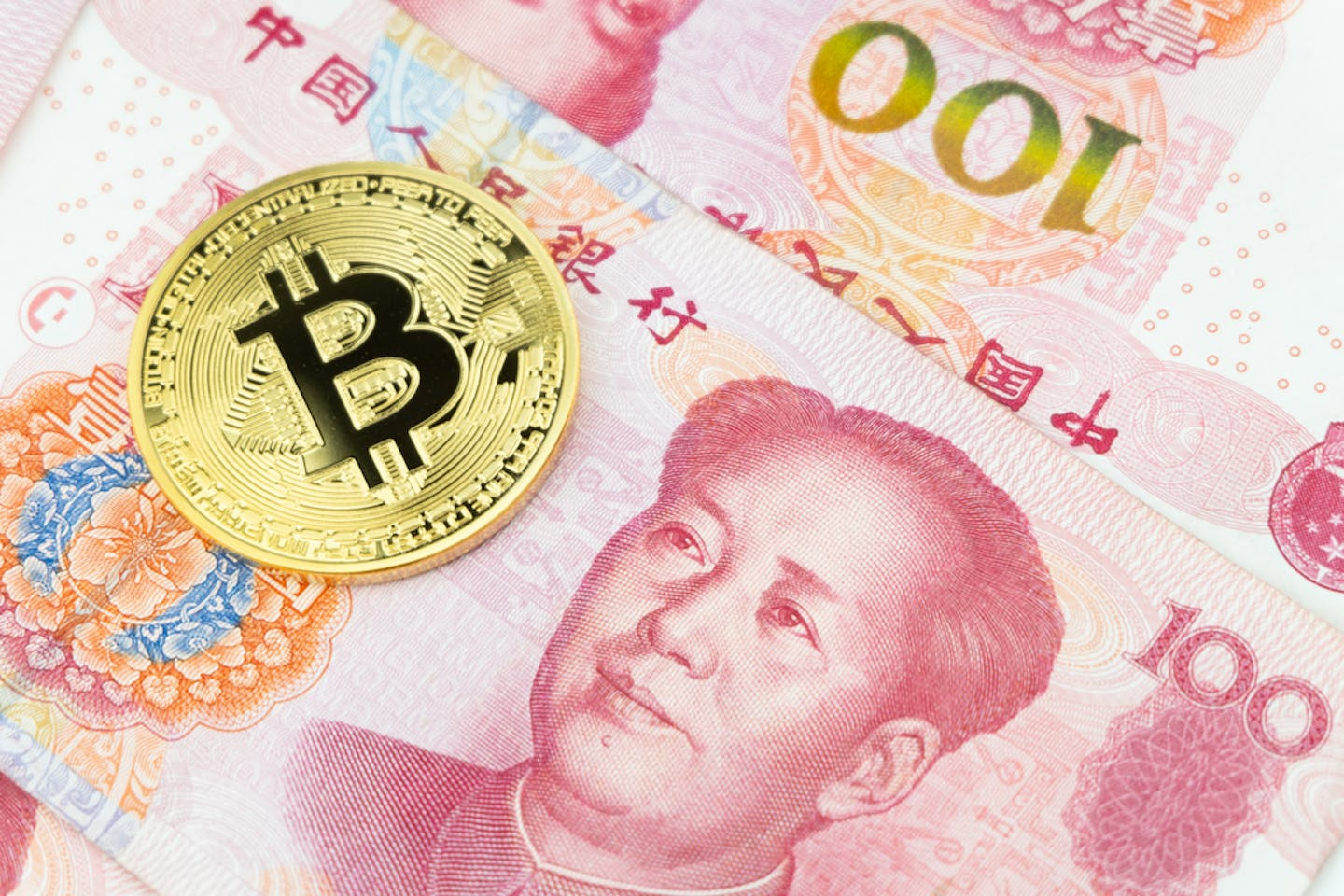 Golden bitcoin with Chinese yuan banknotes