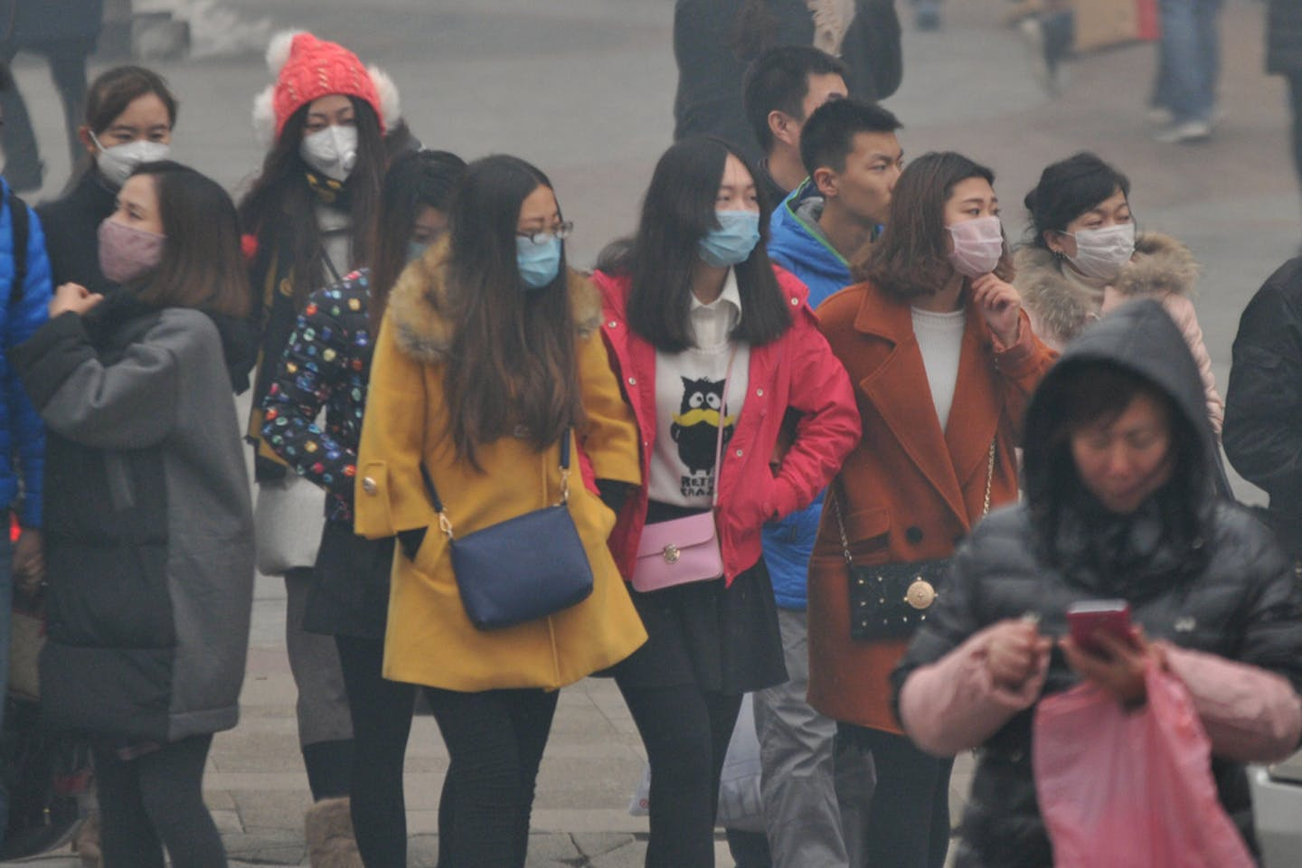 pedestrians walking in smog in shenyang city china
