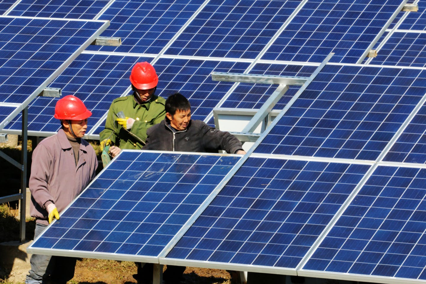 Chinese workers install solar panels