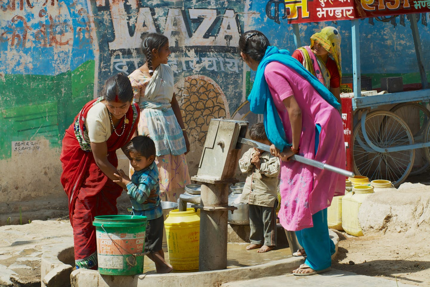 women and children pump water to plastic containers in Orchha, India