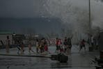 Children gather by the seawall as strong waves brought by Typhoon Kammuri