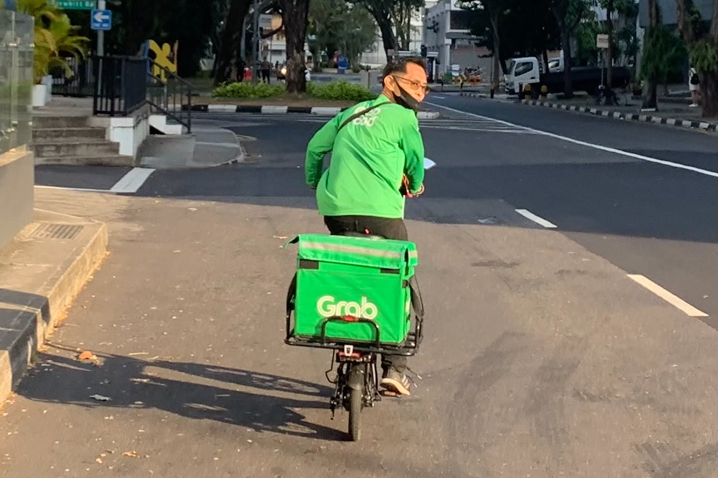 A GrabFood driver riding an e-scooter in Little India, Singapore.