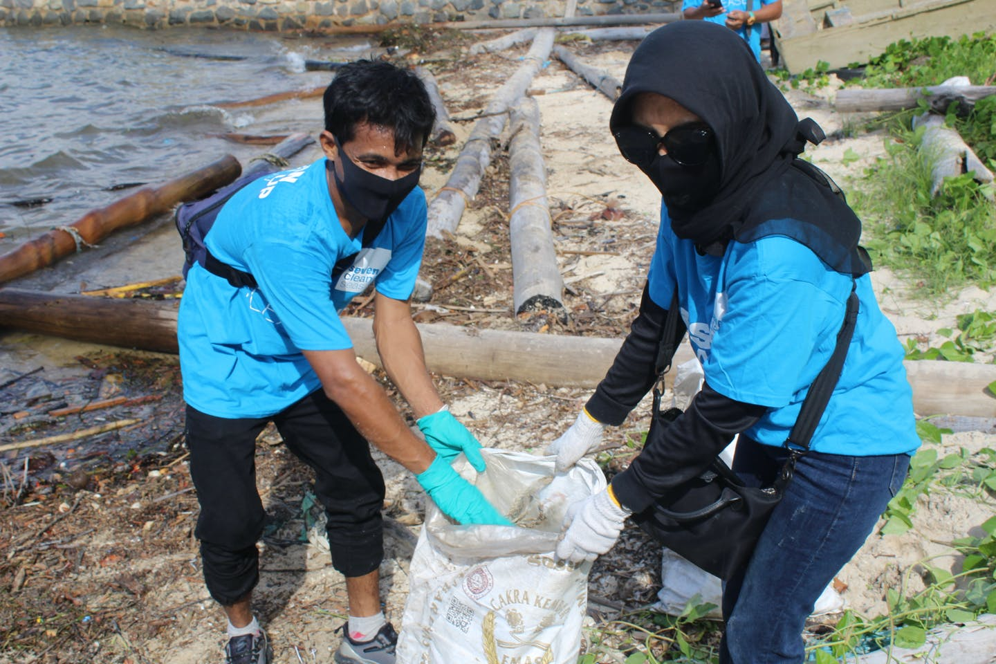 Hospitality workers lift a sack of collected marine debris from a beach in eastern Bintan, Indonesia.