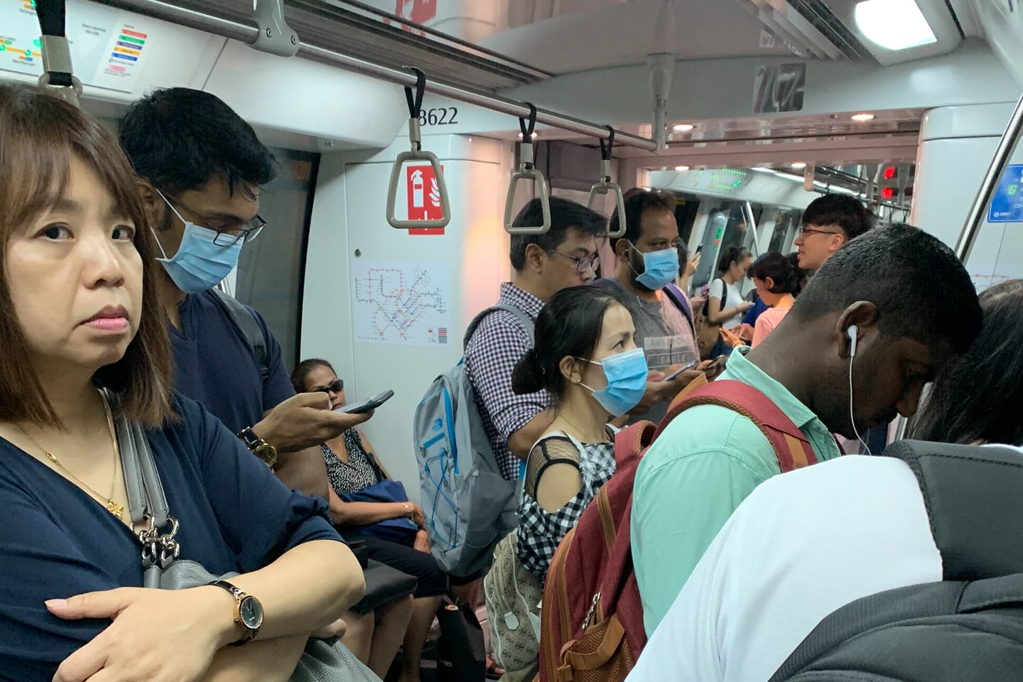 Commuters on a train in Singapore, some wearing disposable surgical masks as a protection measure from the Coronavirus. Image: Eco-Business