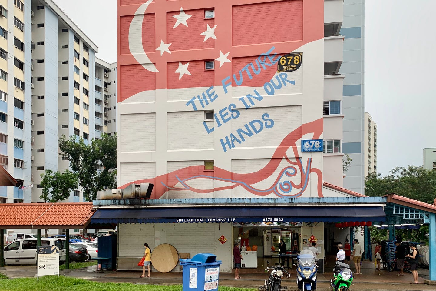 "A mural painted on a wall in the heartland district of Hougang, Singapore, reads: ""The future lies in our hands"". Image: Robin Hicks/Eco-Business"