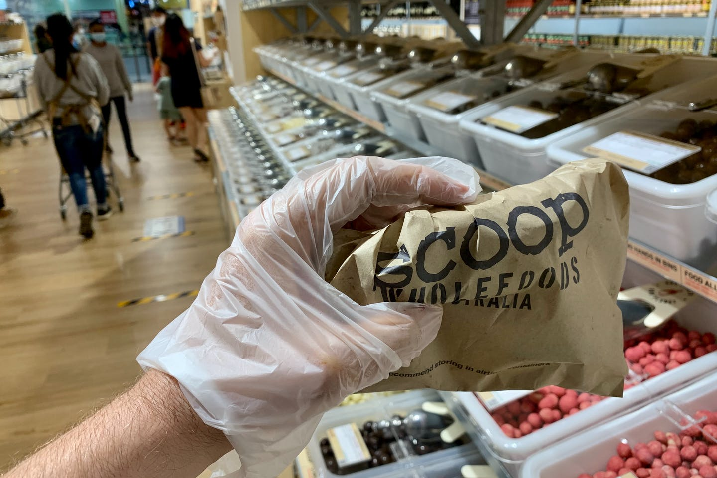 A customer using a disposable plastic glove holds a paper bag of products at a Scoop store in Singapore.