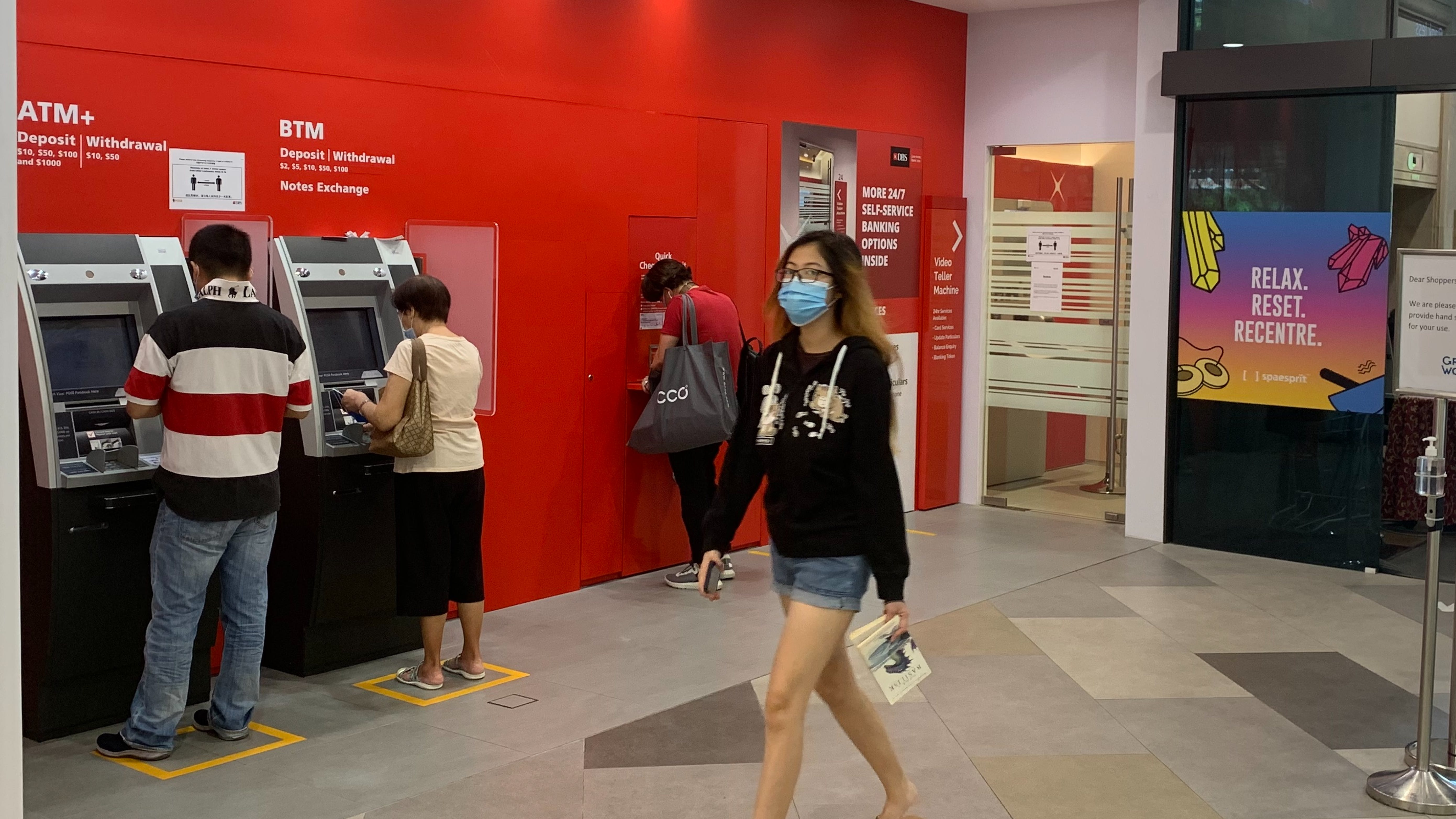 People using ATM machines in Singapore. Image: Robin Hicks/Eco-Business