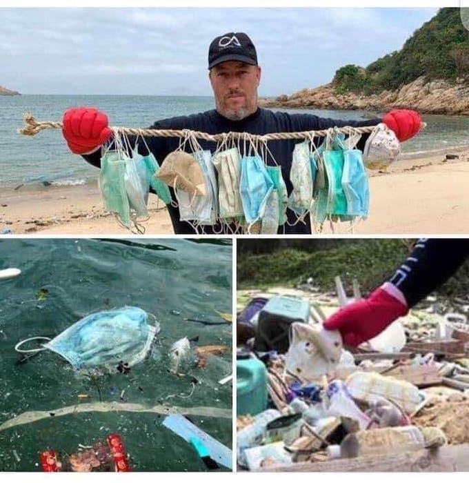 A man retrieves face masks from the sea