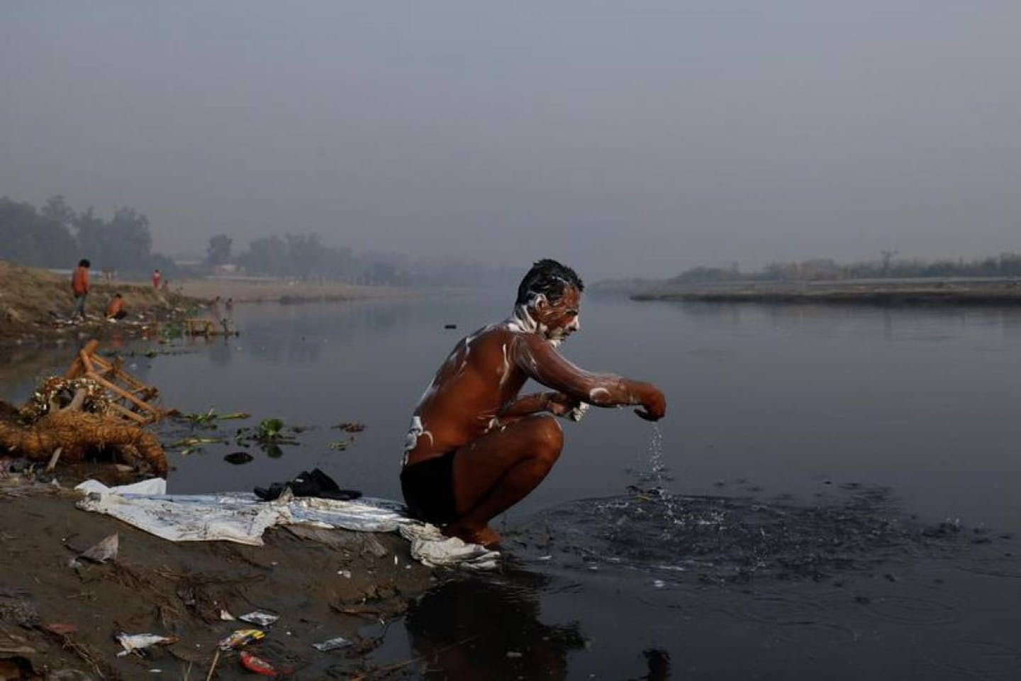 man washes in polluted water