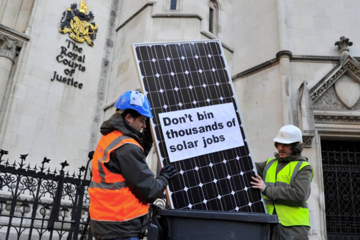 Panel installers pose with a solar panel outside the High Court in central London.