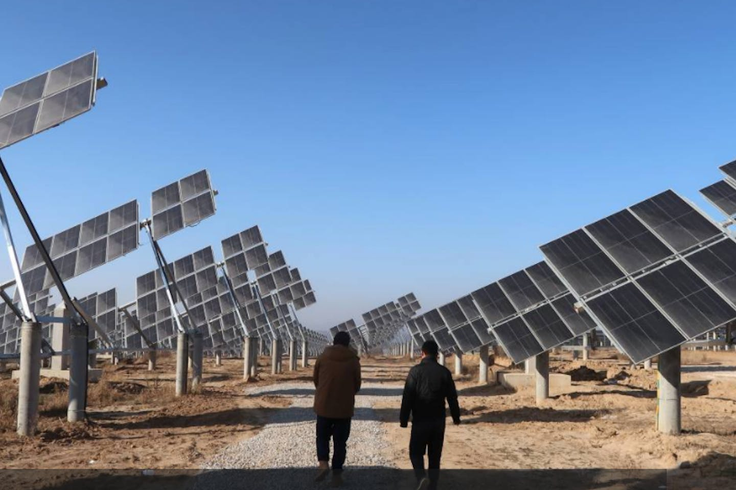 Workers walk at a solar power station in Tongchuan, Shaanxi province, China