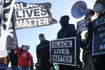 Black Lives Matter demonstrators hold signs during a march in St Paul, Minnesota, US.