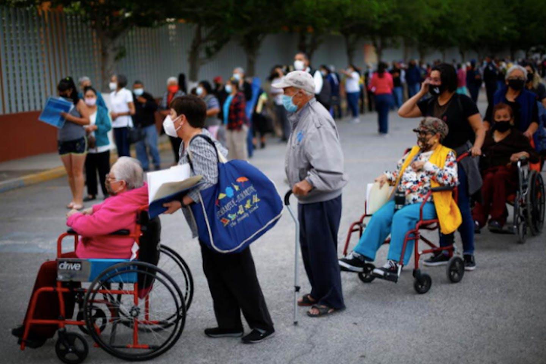 Elderly people queue for vaccination