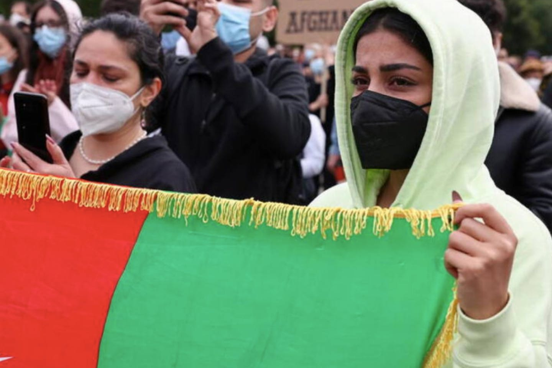 woman holds an Afghan flag
