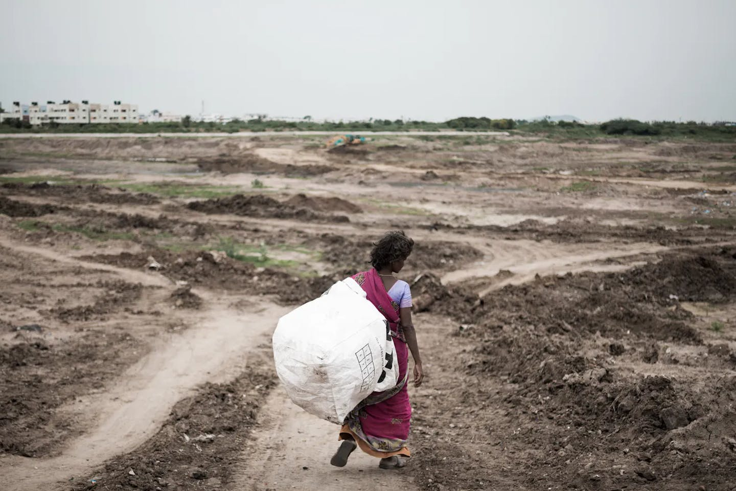 A woman walks into dried-up Narayanapuram Lake to collect waste to be sold in the scrap market