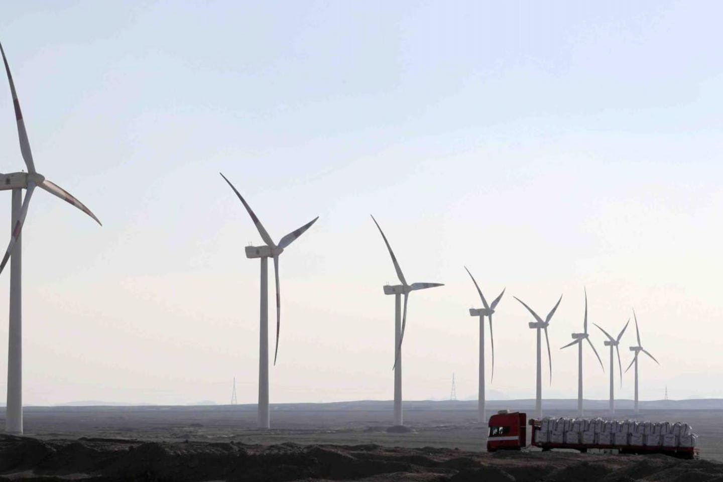 A truck moves past power-generating wind turbines