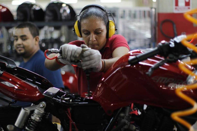 a woman assembles motorbike