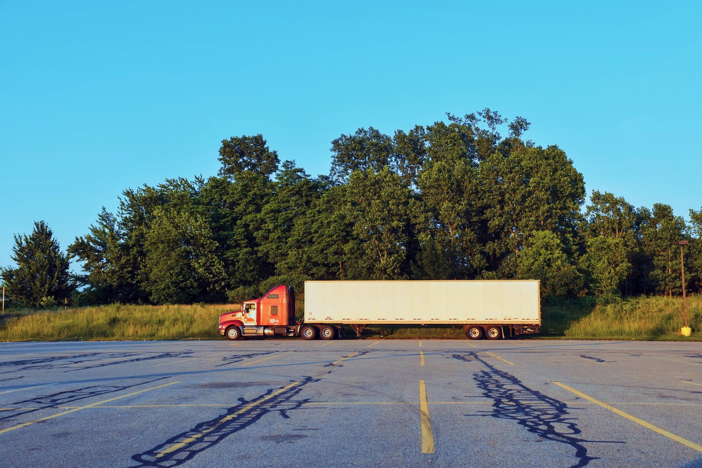 A freight truck sits in a parking lot.