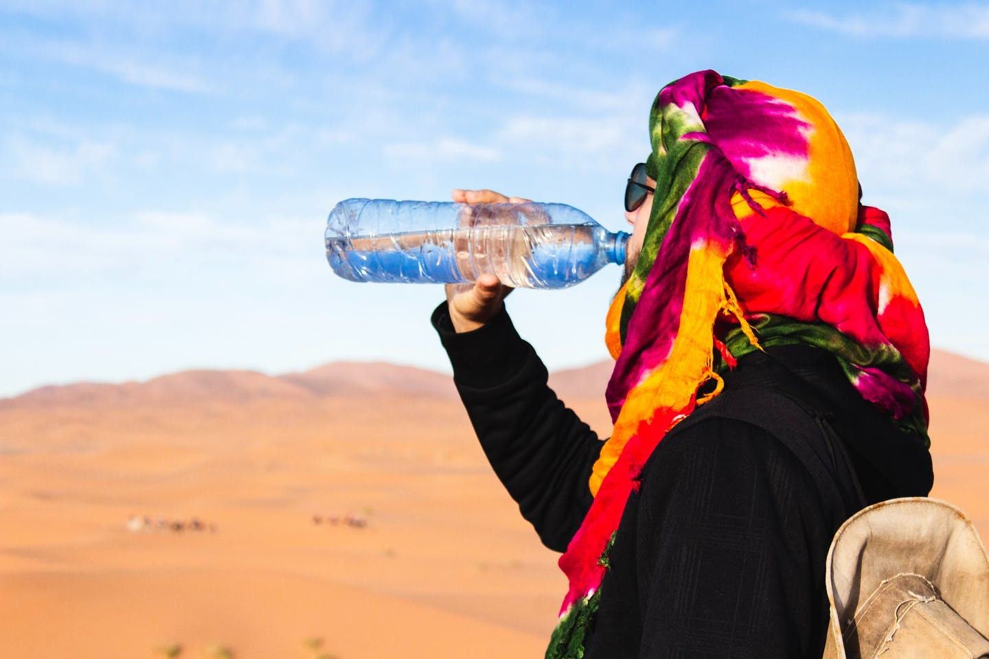 Traveller drinks water from a plastic bottle