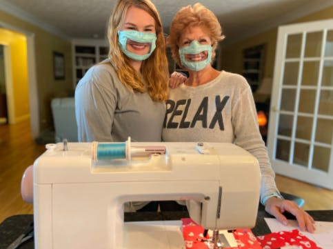 Ashley Lawrence (left) poses with her mother while they both wear a mask made for the deaf and hard of hearing community.