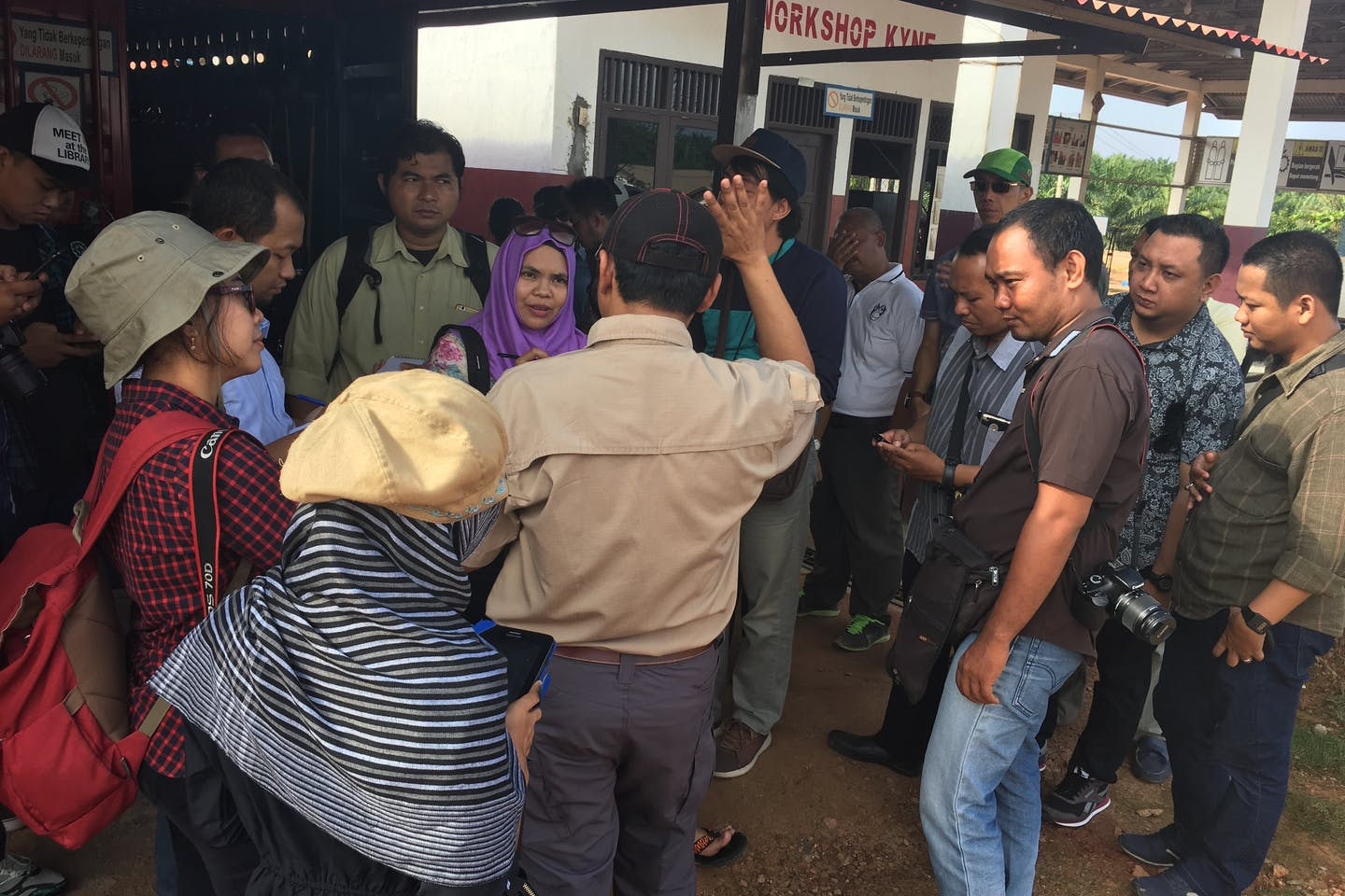 Journalists at a palm oil plantation question a corporate communications official.