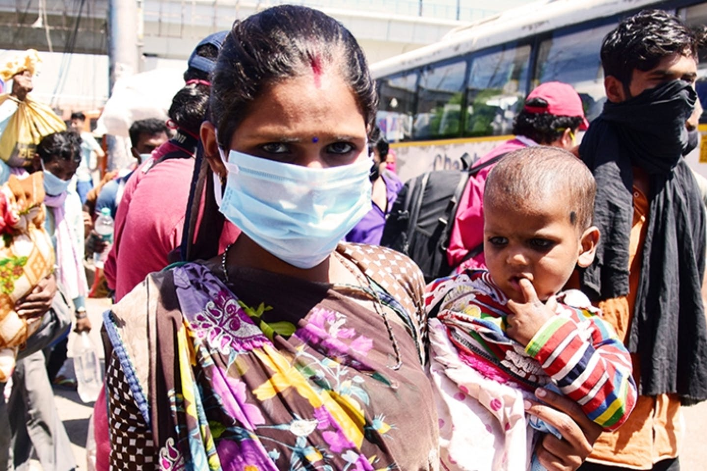 A woman with her baby at a bus stop in Delhi. Women in developing countries are being hit hardest by the coronavirus pandemic. Image: rajput/SOPA Images/Shutterstock