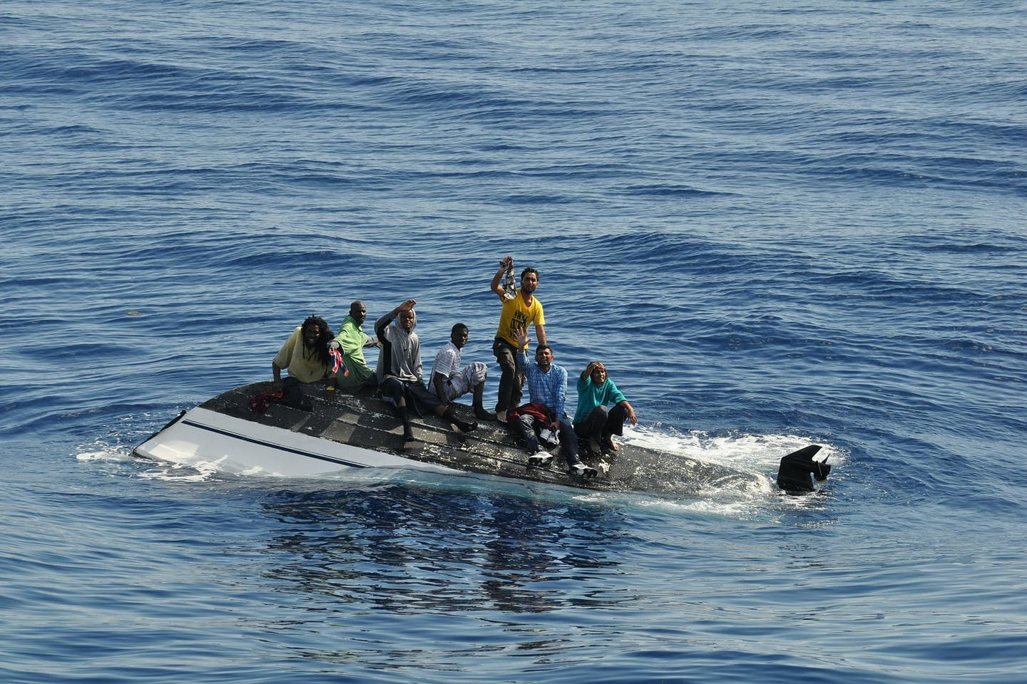 migrants on top of a capsized vessel