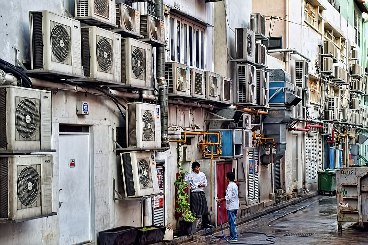 Air conditioner compressors occupy almost all the open space available on the wall of a building in Boat Quay, Singapore