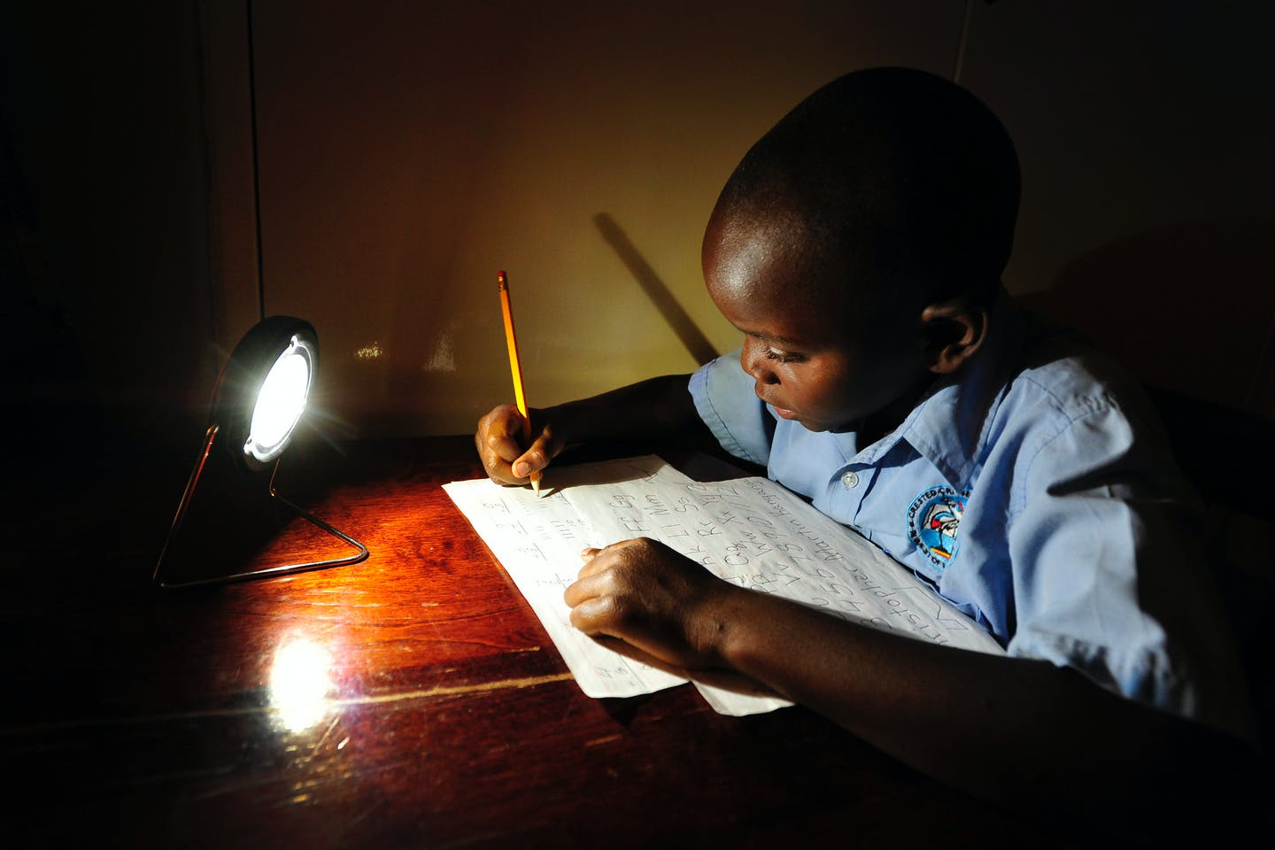 boy studying under solar lamp