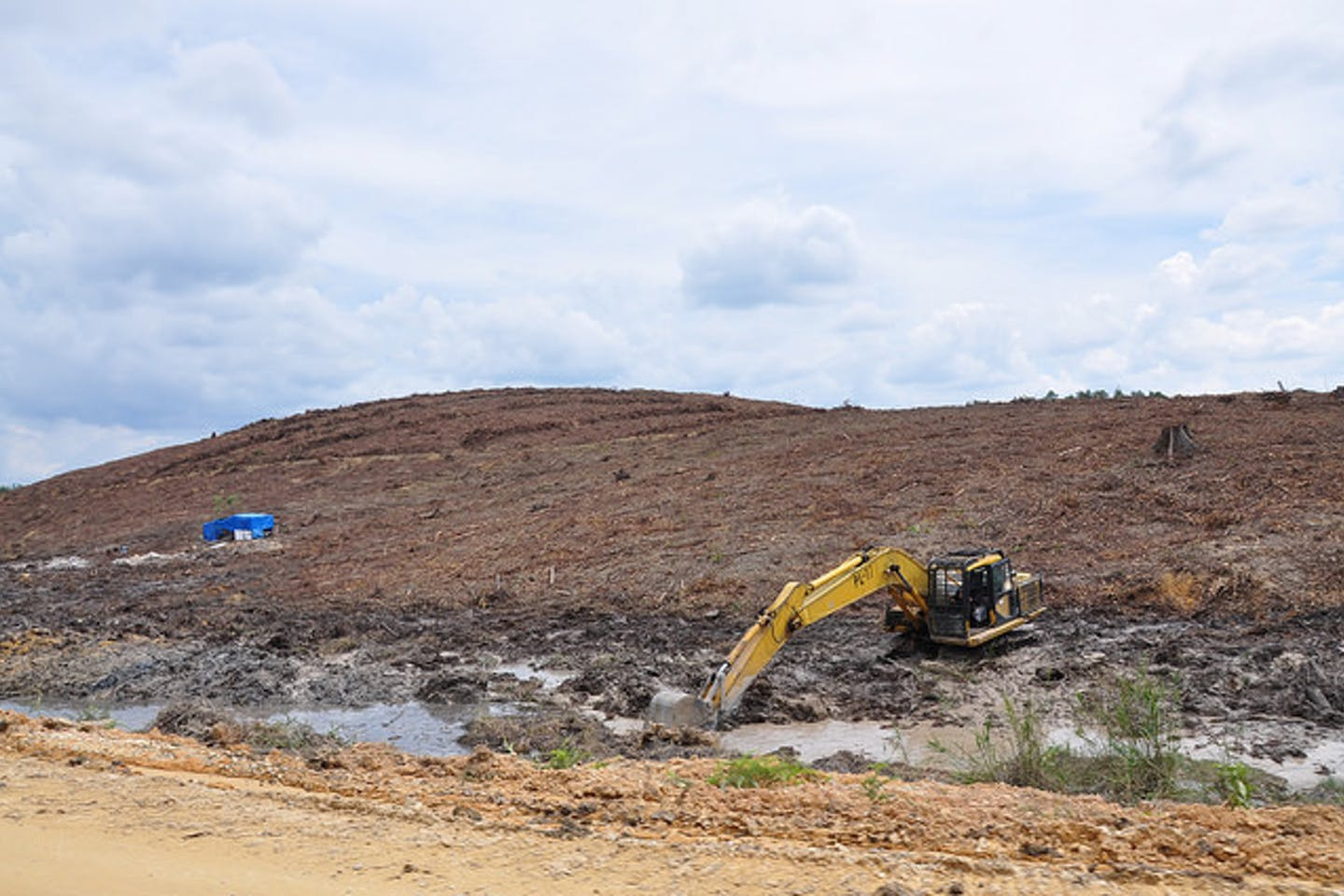 tractor ploughs through burned peat