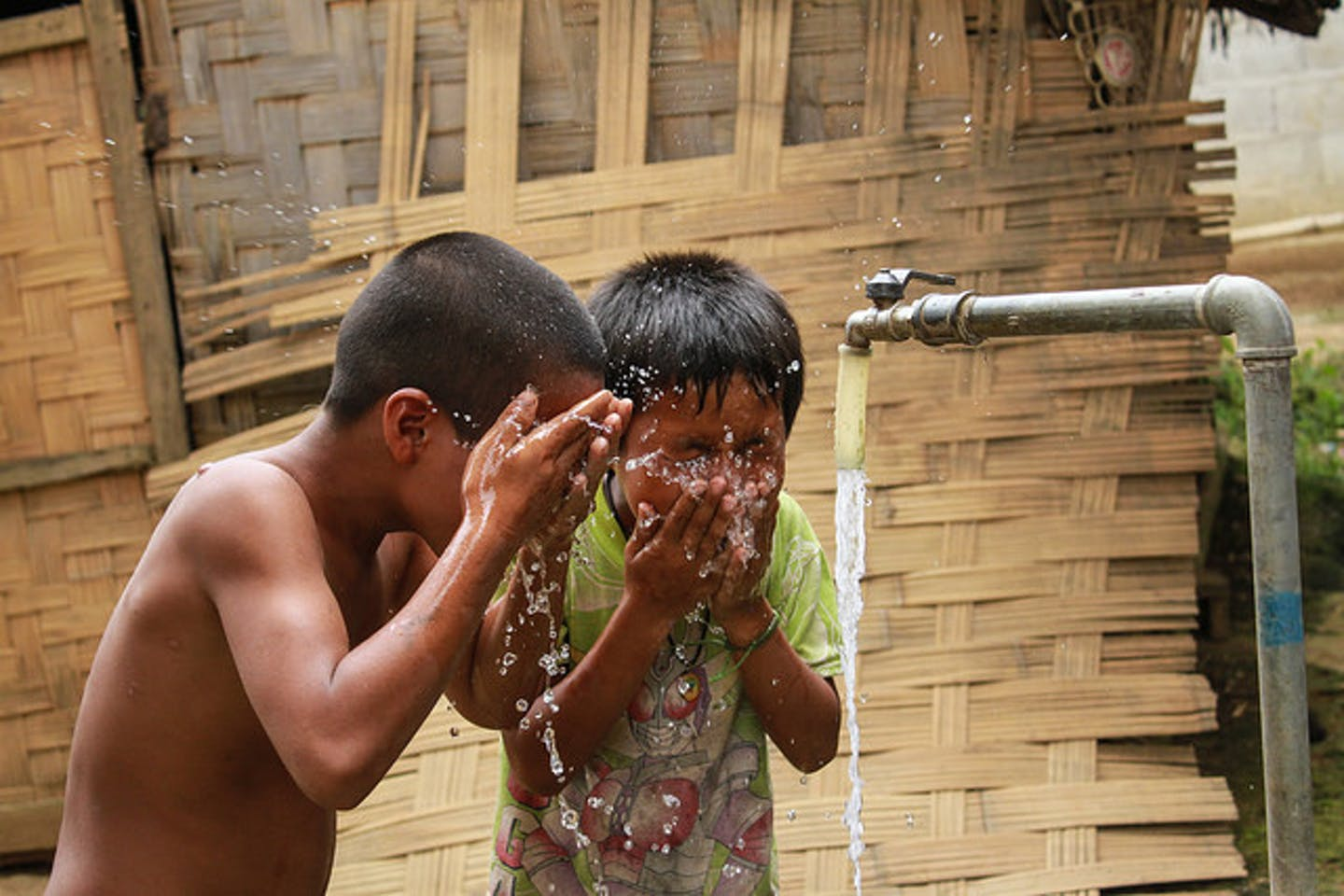 kids cool off with clean water in LAO