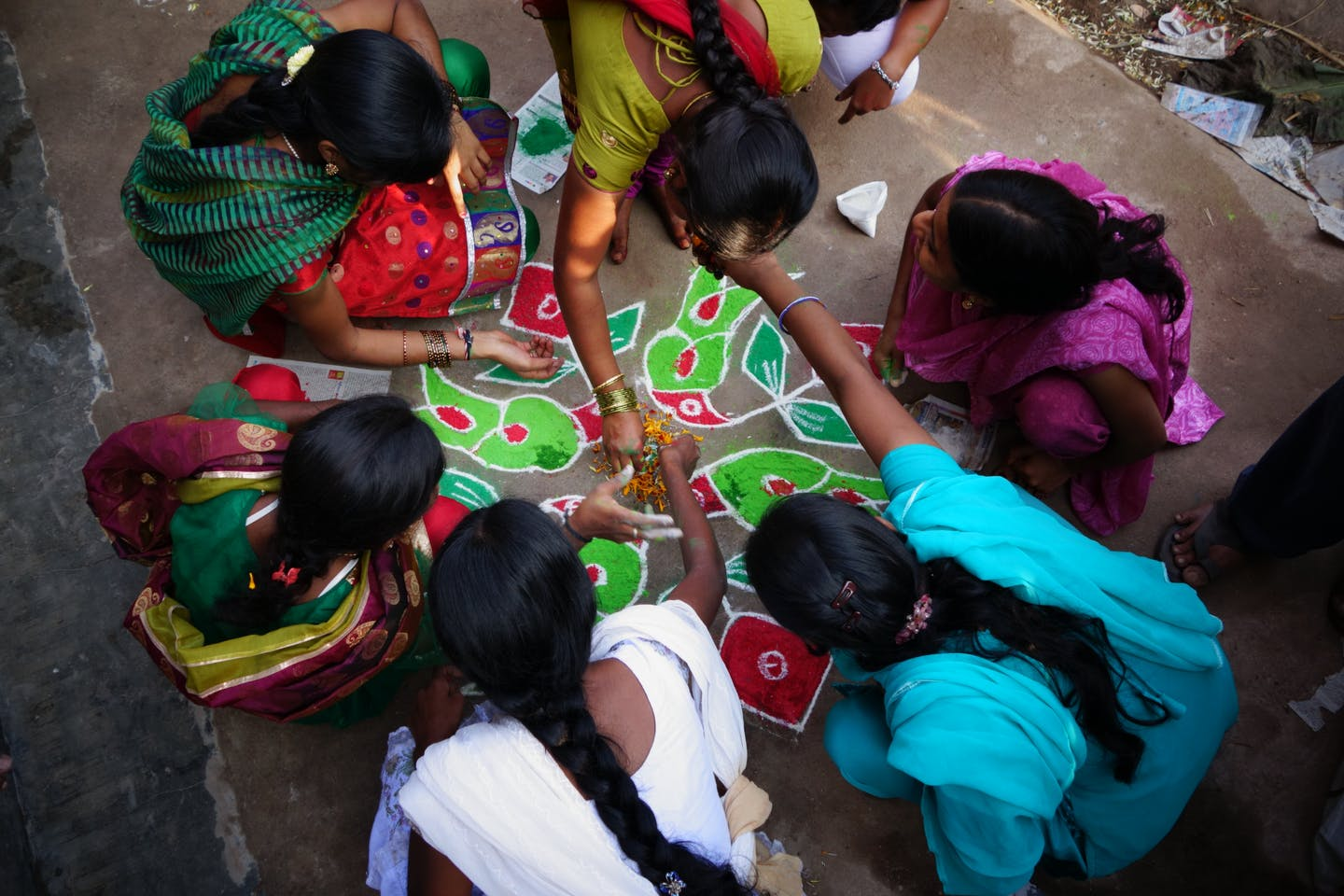 Women drawing rangoli on the floor in India