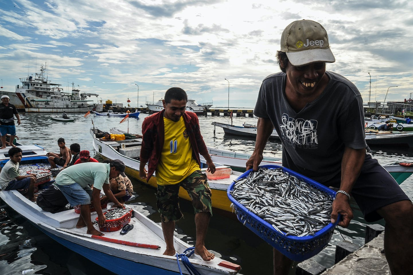 Fishermen unloading buckets of fish from their boats in Makassar, South Sulawesi, Indonesia