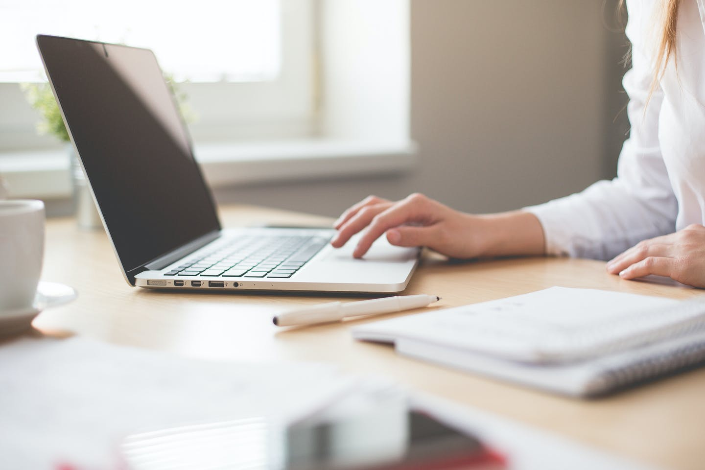 Woman working on her laptop possibly doing sustainability reporting