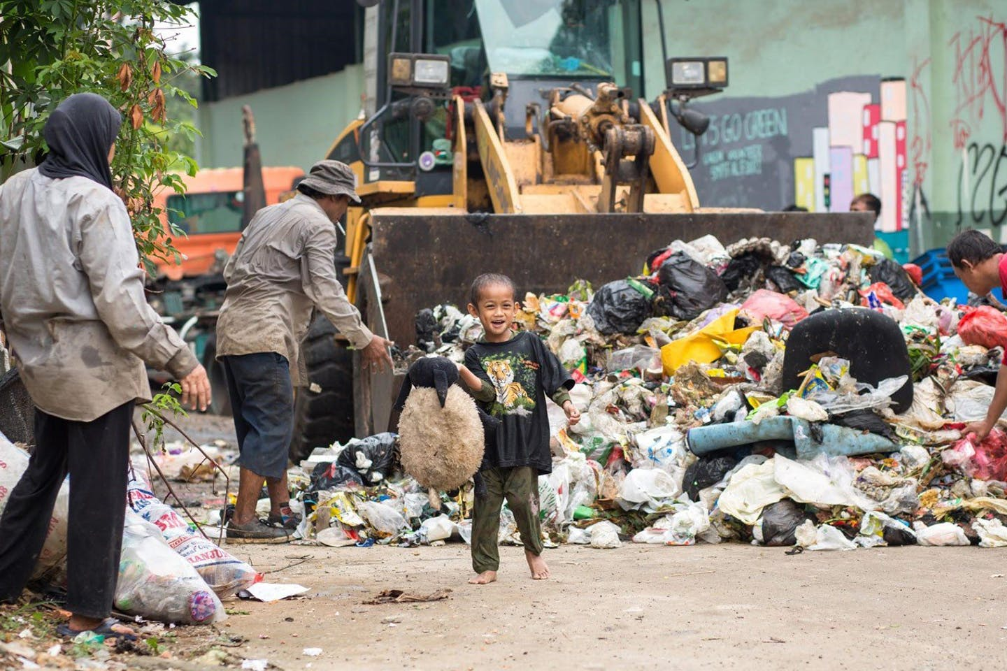 A child finds a teddy bear in a waste bank in Depok, West Java.