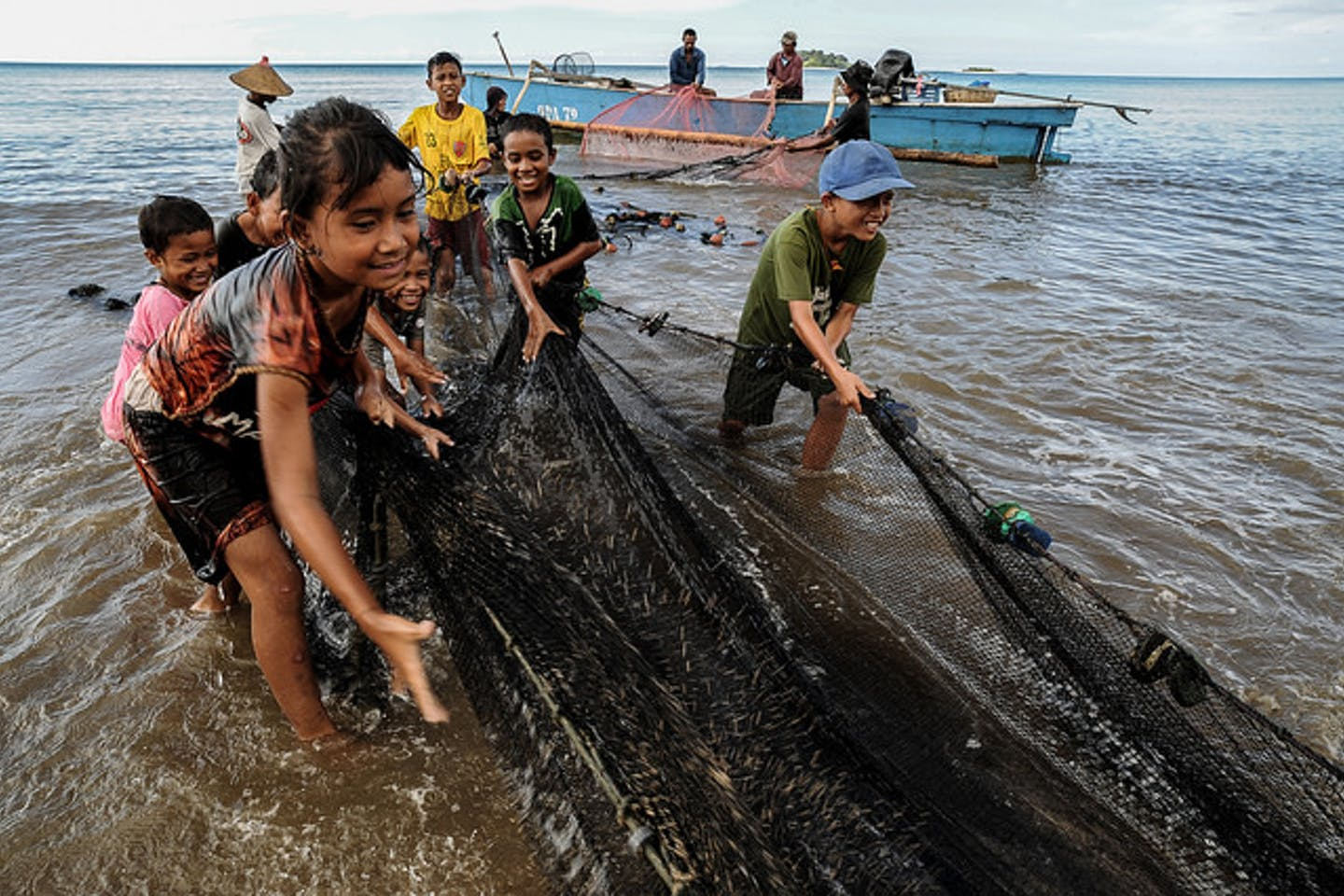 children help pull fishing nets in Indonesia