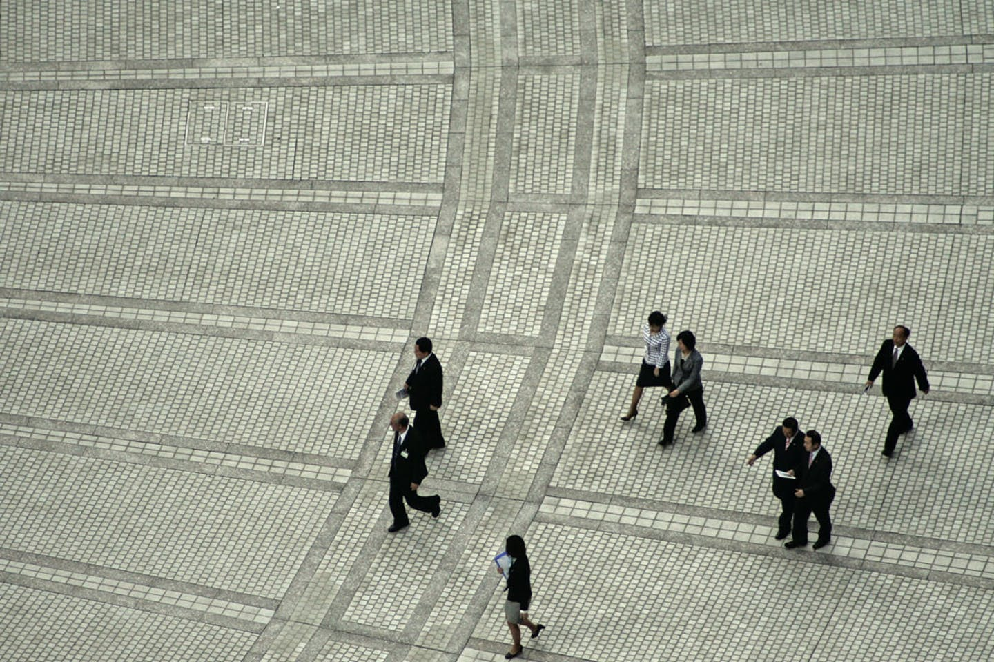 office workers cross a downtown plaza in Tokyo