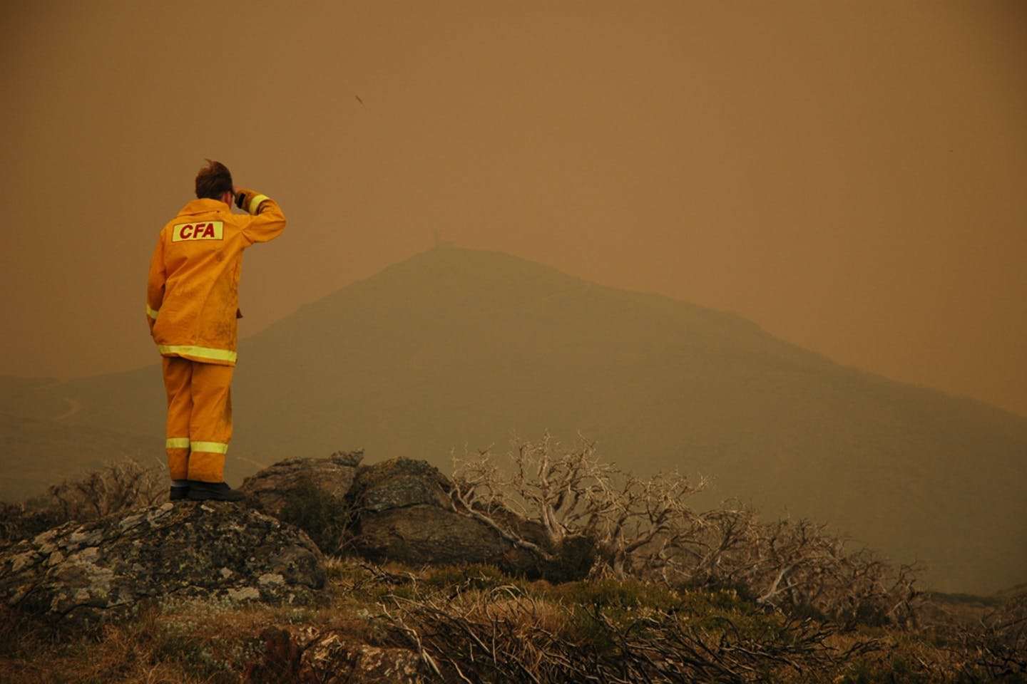 A firefighter in Falls Creek, Victoria, Australia looks across the smog generated by wildfires.
