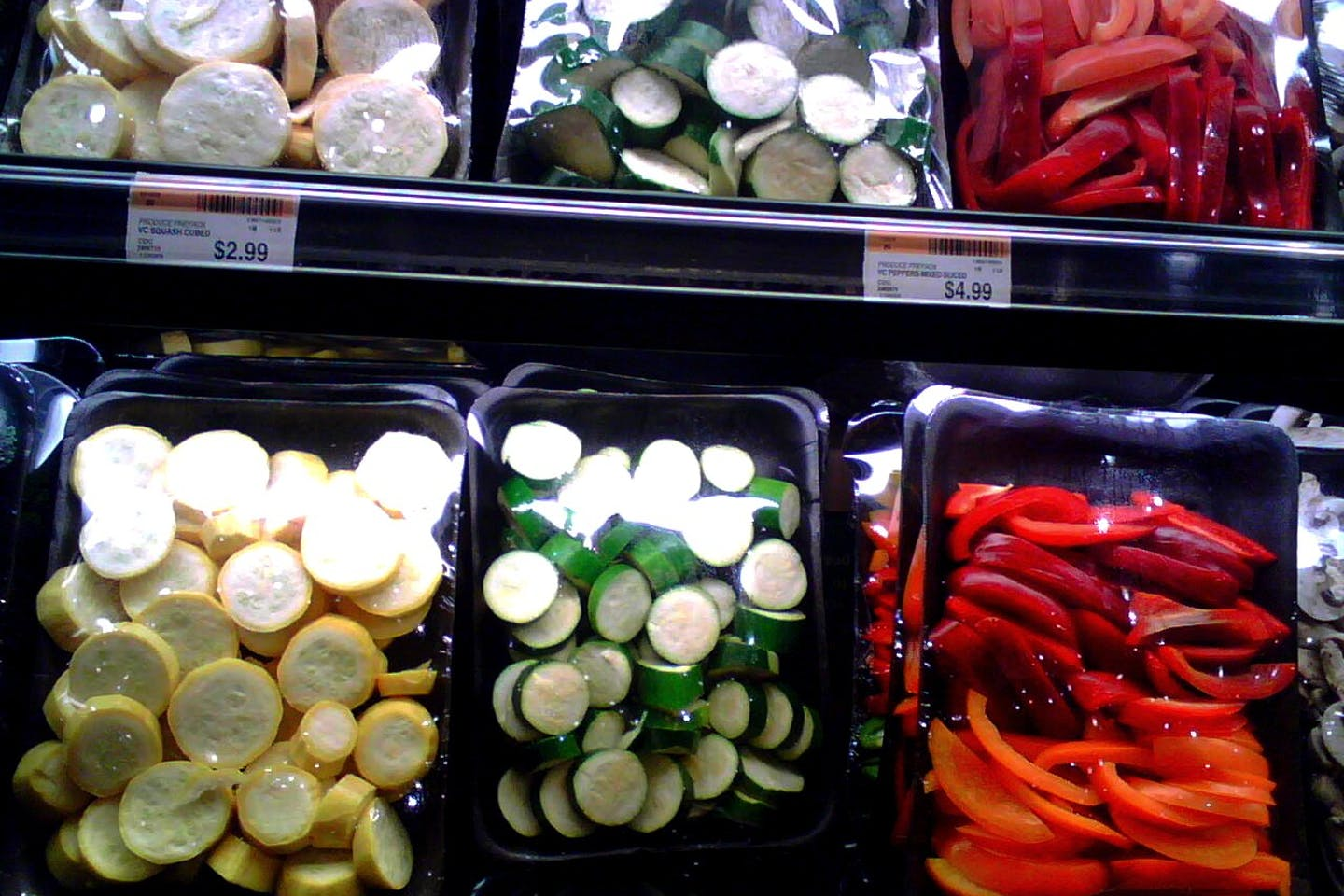 Presliced vegetables in plastic wrapping on supermarket shelves