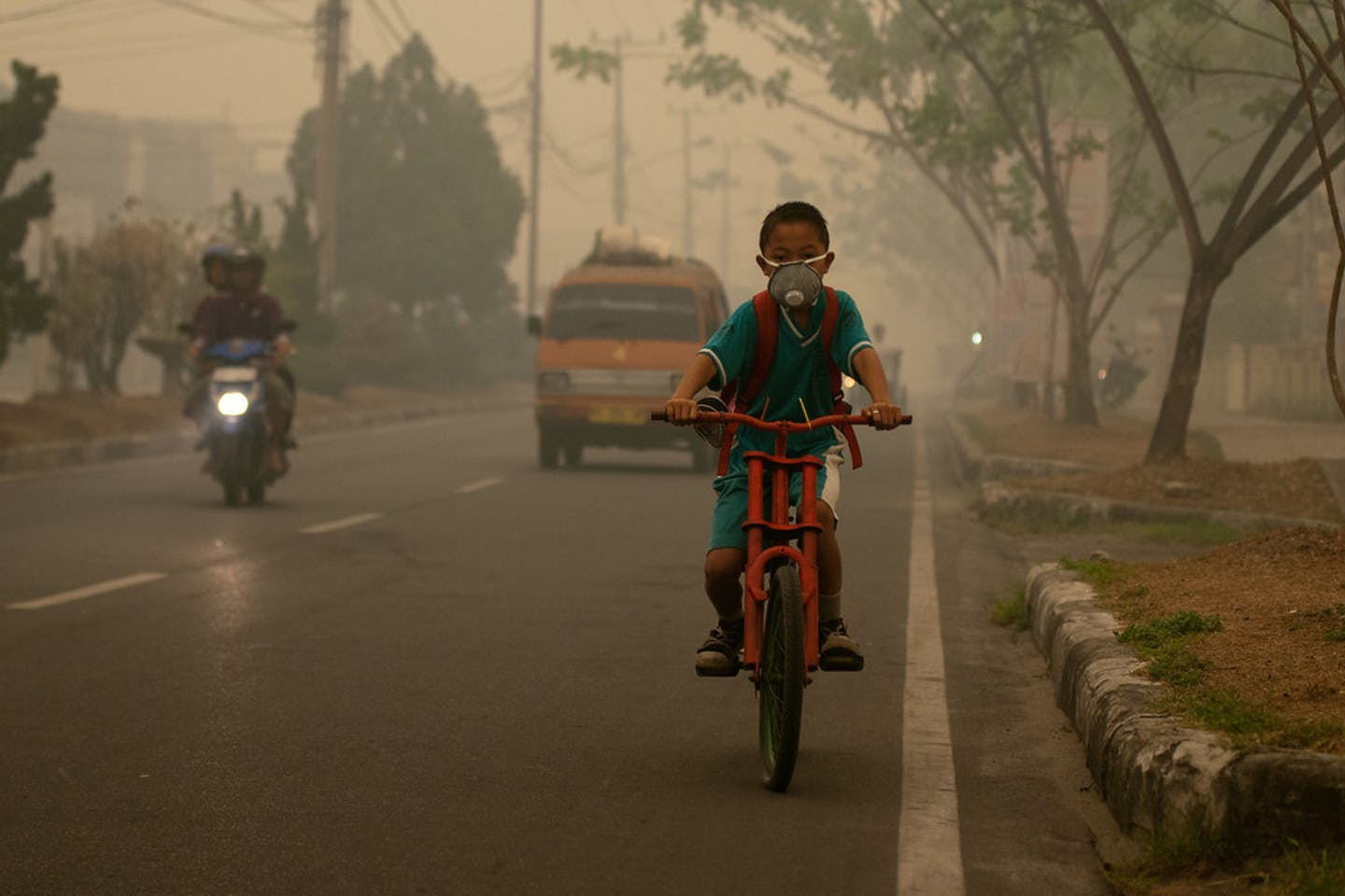 boy biking pollution indonesia