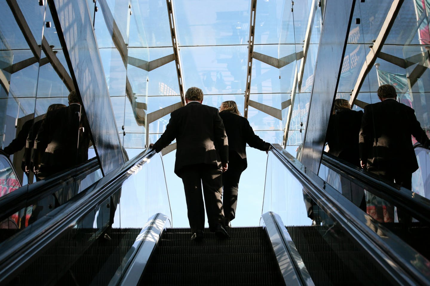 Business man and business woman on an escalator against blue sky