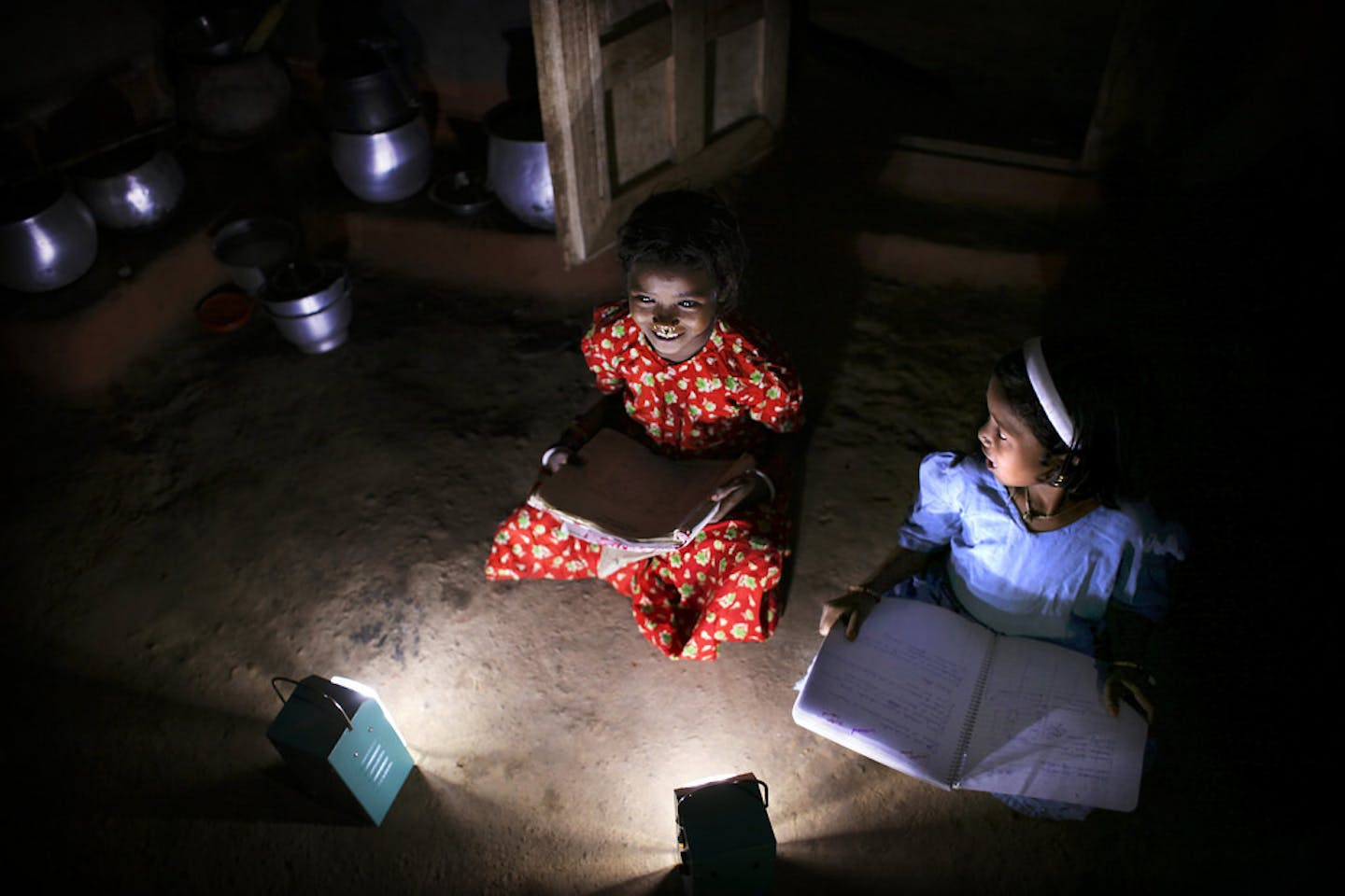 Girls in a village in India read books after dark with the help of solar lamps
