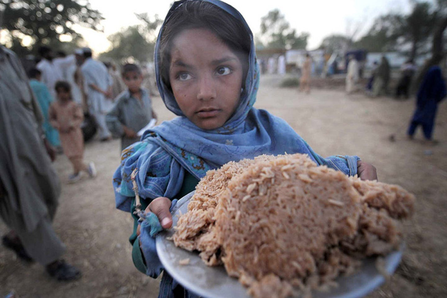 child holds a plateful of rice