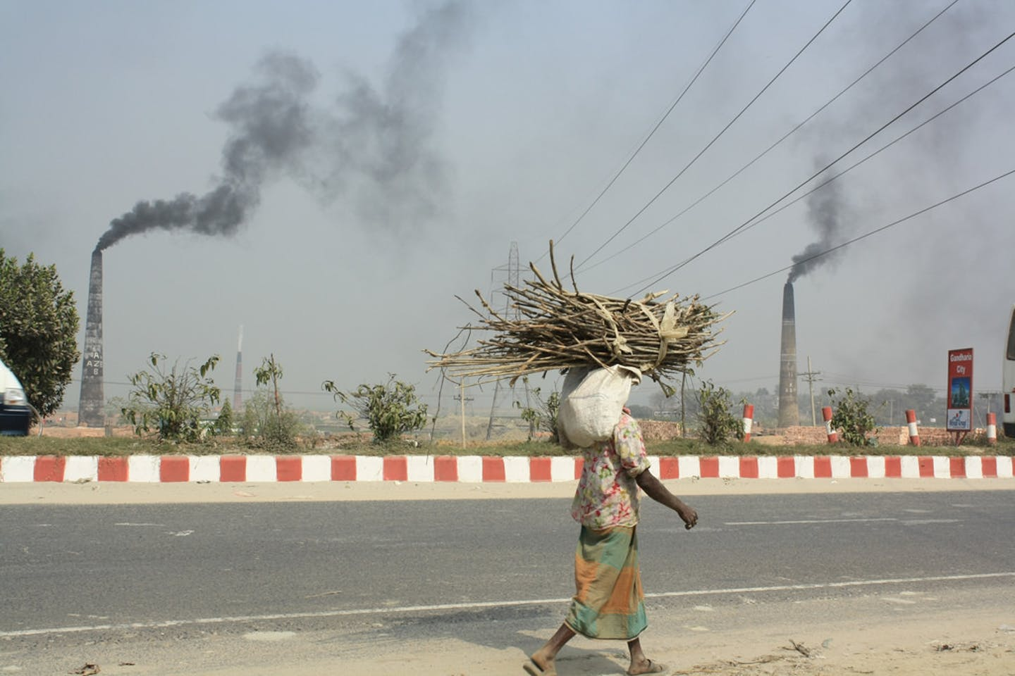 A man carries firewood past the smoking stacks of brick kilns Dhaka