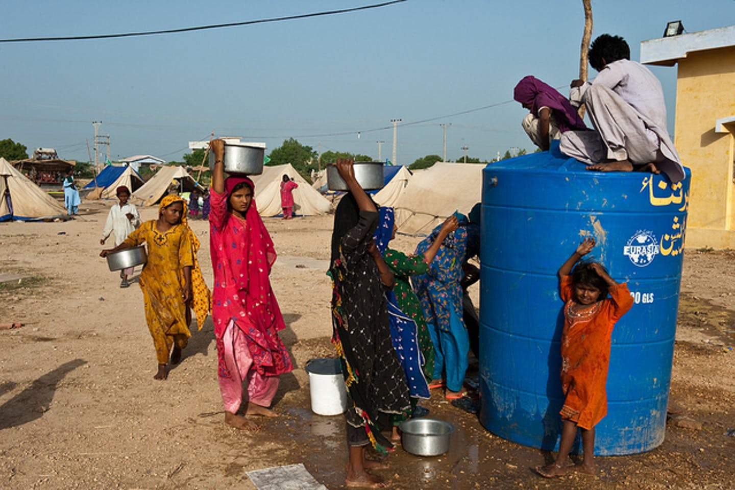 Women and children displaced by floods in Pakistan queue for water.