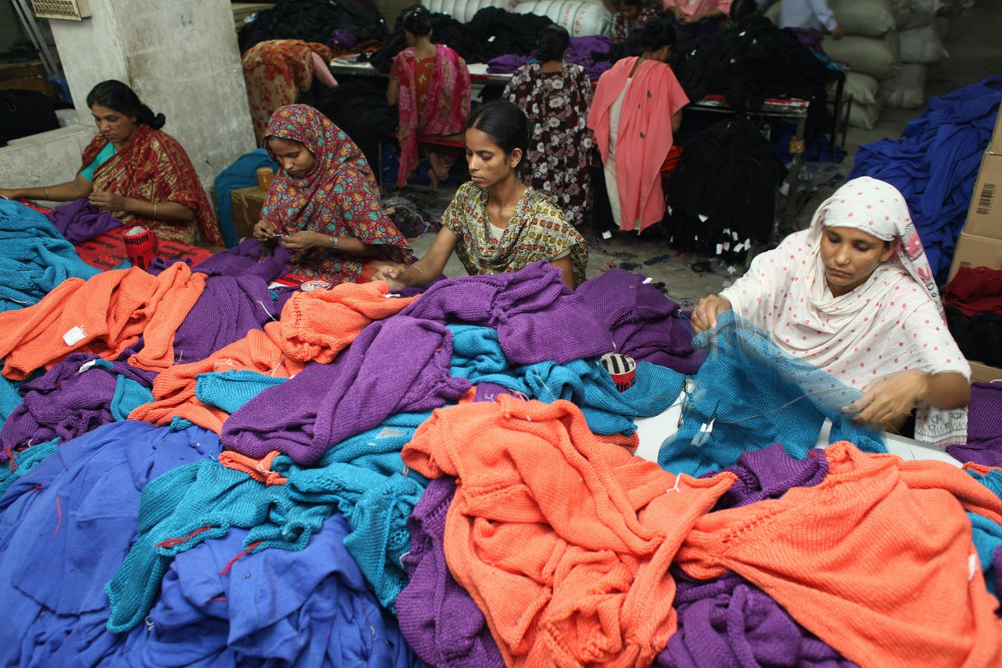 Women sort and check the finished products in the manufacturing plant of the Wool Tex Sweaters Limited in Shewrapara, Dhaka, Bangladesh
