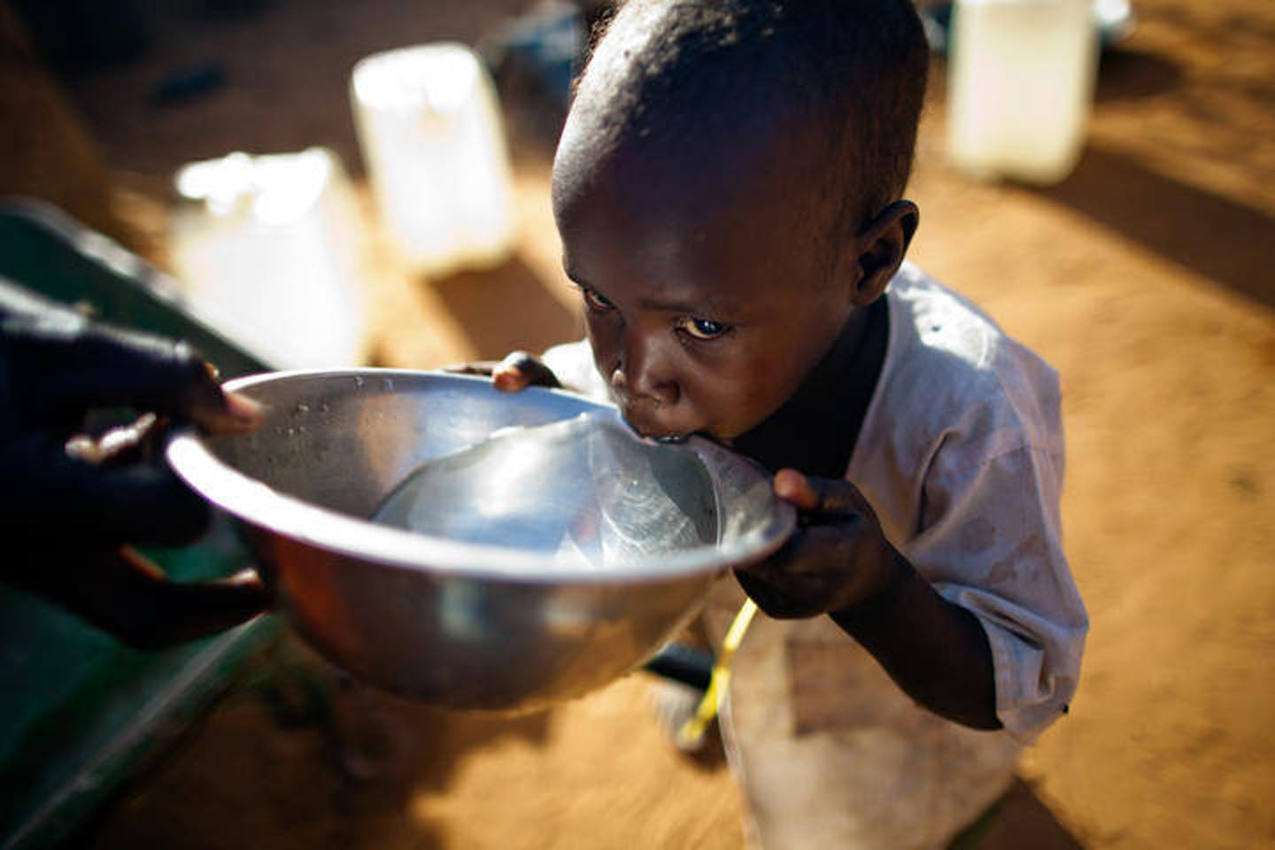 child receives a drink of water in Sudan